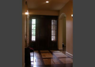 The entry door is hand hewned, and the entry way has tumbled travertine flooring framed by hand hewned wooden planks. The kitchen has custom cabinetry and antiqued granite countertops.